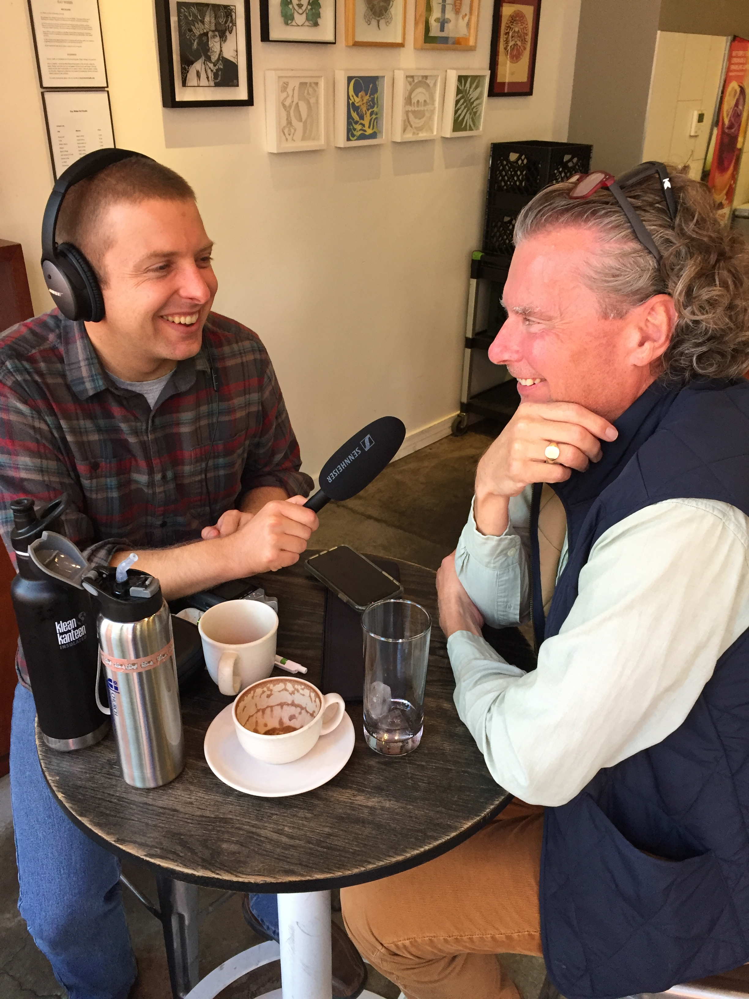 Kyle, wearing headphones, holds mic up to study participant Sam in a coffee shop.