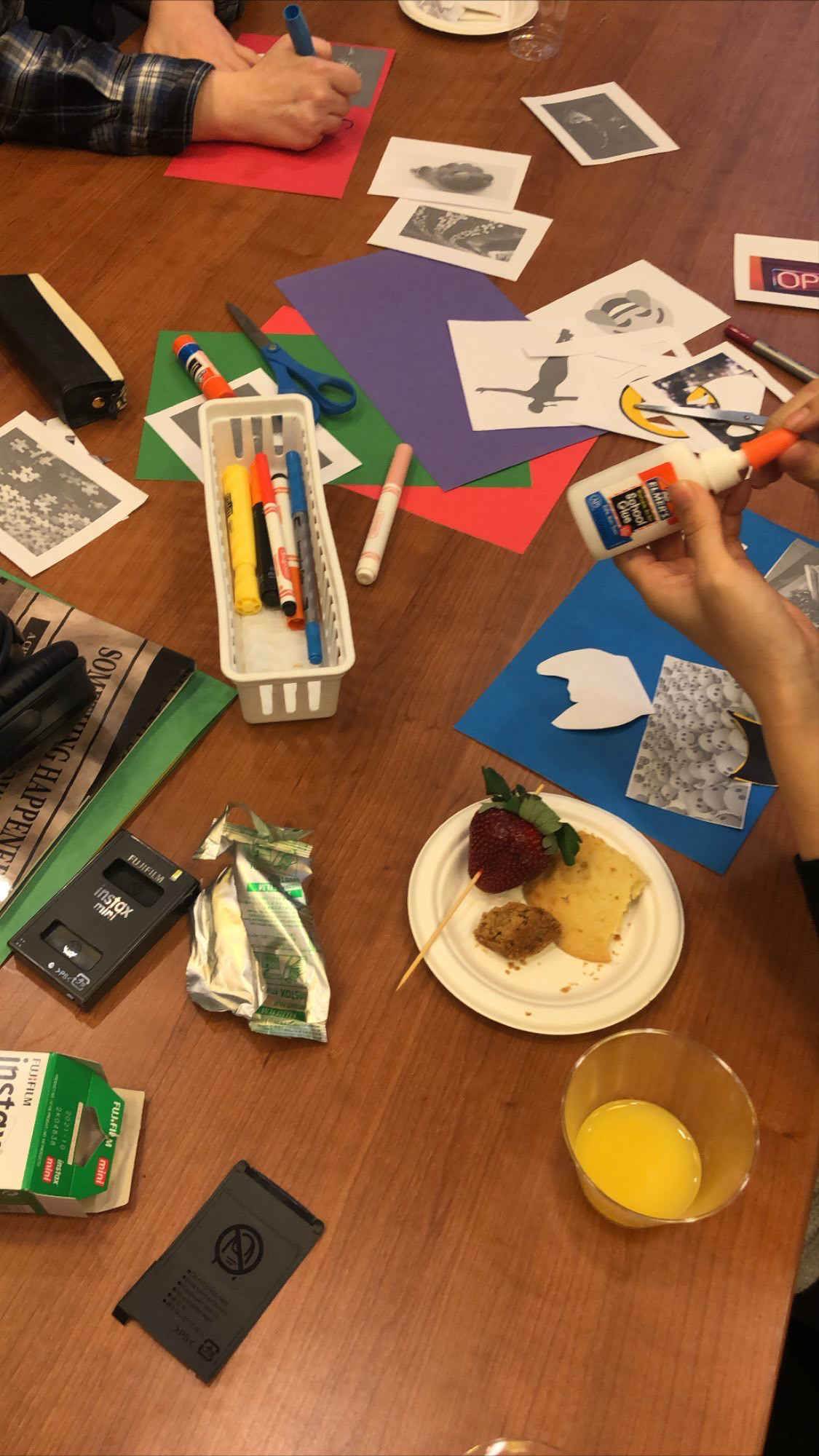 birds eye view of a table with construction paper, glue, markers. There is a glass of orange juice and plate with fruit alongside two sets of hands working on collaging.