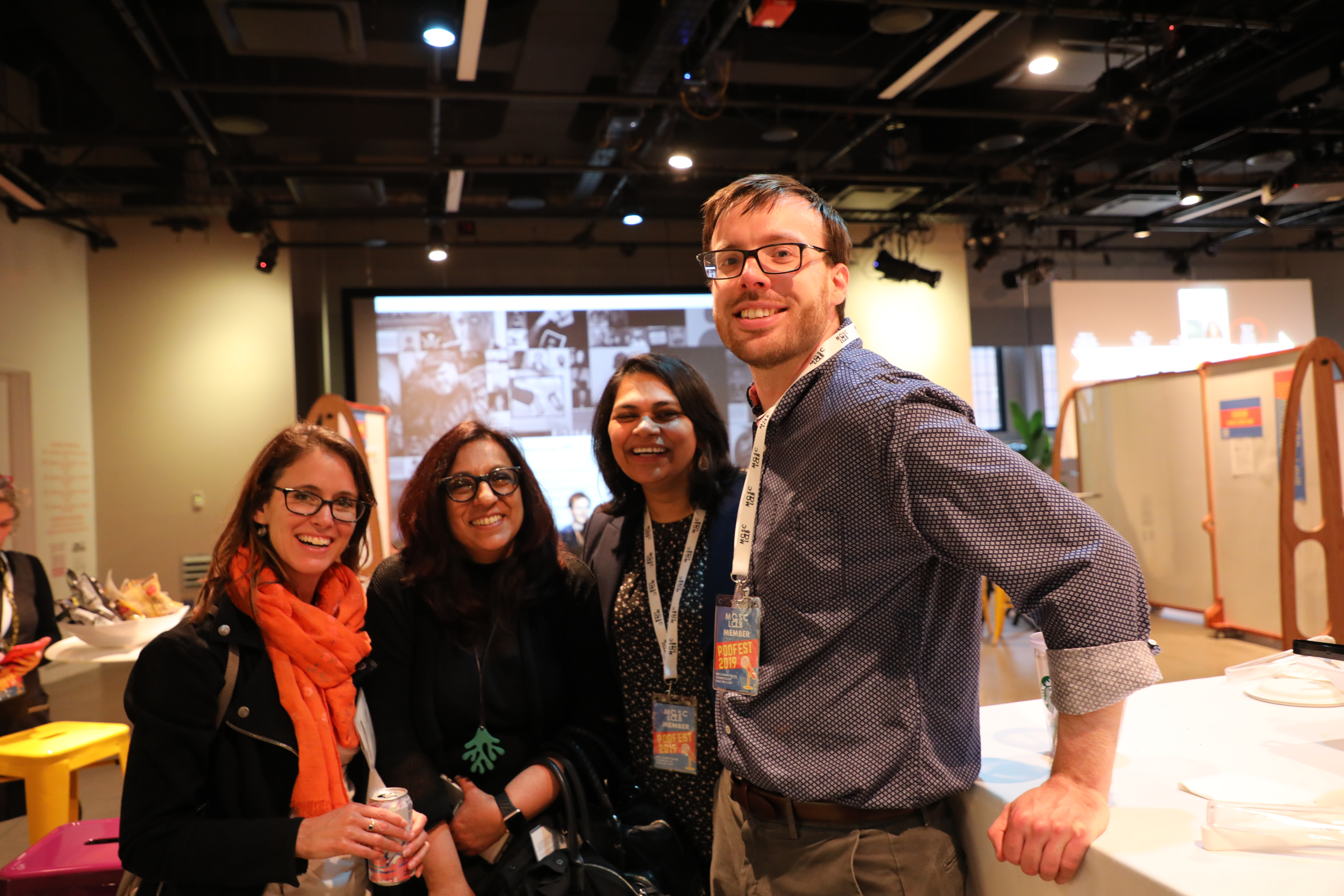 four people (joe, lalitha, ambreen and laura) standing and smiling at camera with sceen projecting in background in exhibit space (smith learning theater)