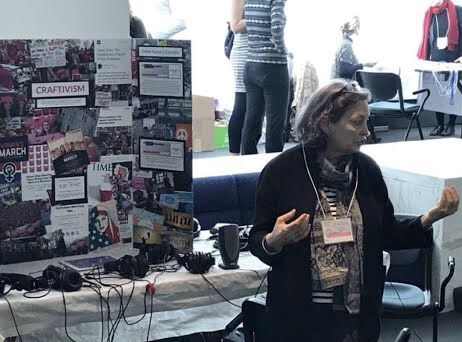 MascLab member Dr. Sandra Markus presenting at a conference about her dissertation work and the creation of the Craftivism podcast. She is standing in front of a conference table with a large trifold poster board with collage images about the Craftivism podcast episode.