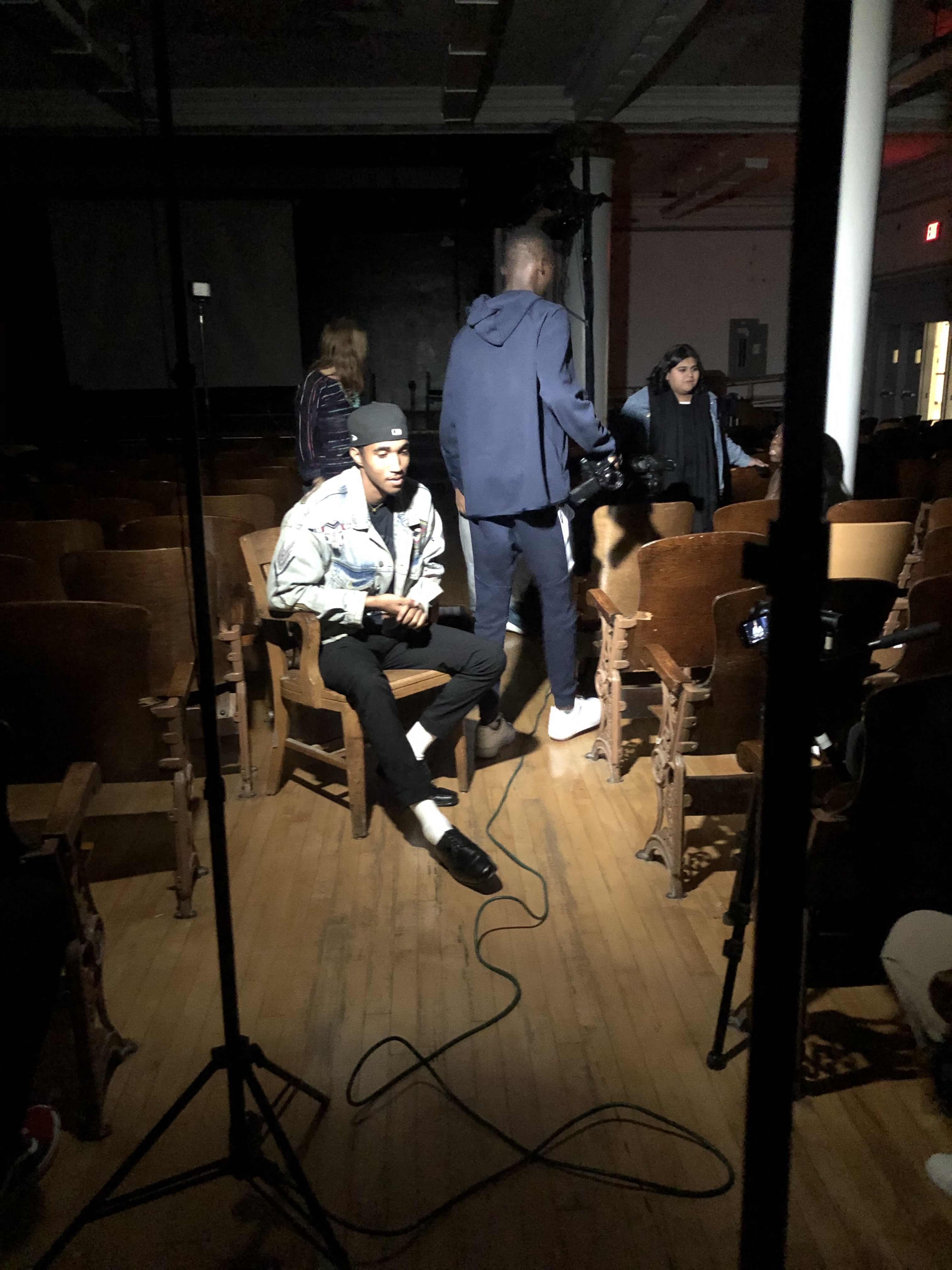 image of youth setting up to record video in a darkened room. One youth is seated towards middle of photo illuminated by a spot light. The other young people are standing towards back of photo with their backs to the camera.