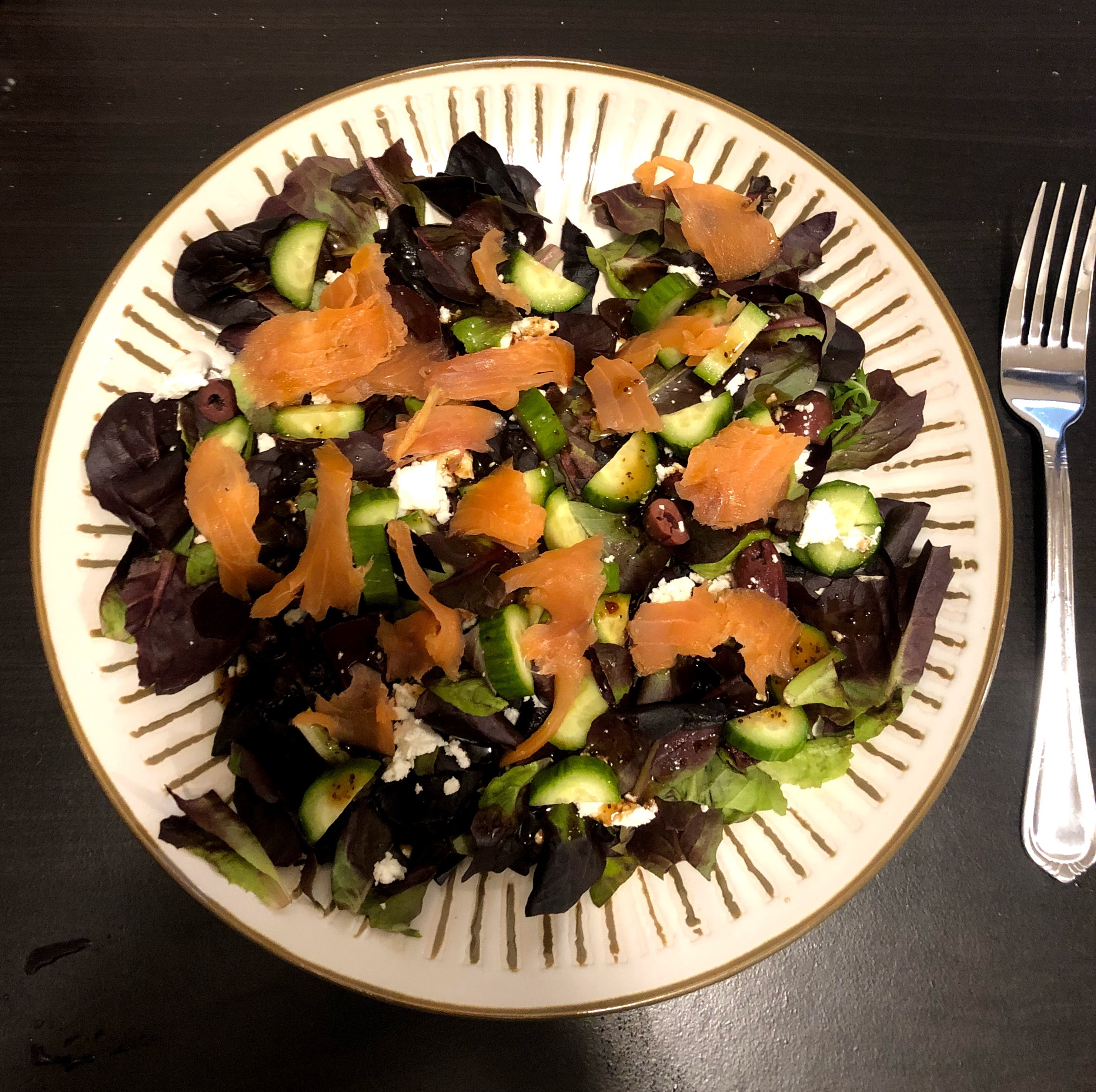 a salad on a plate with a fork, with olives cucumber, white cheese, dark greens, and smoked salmon