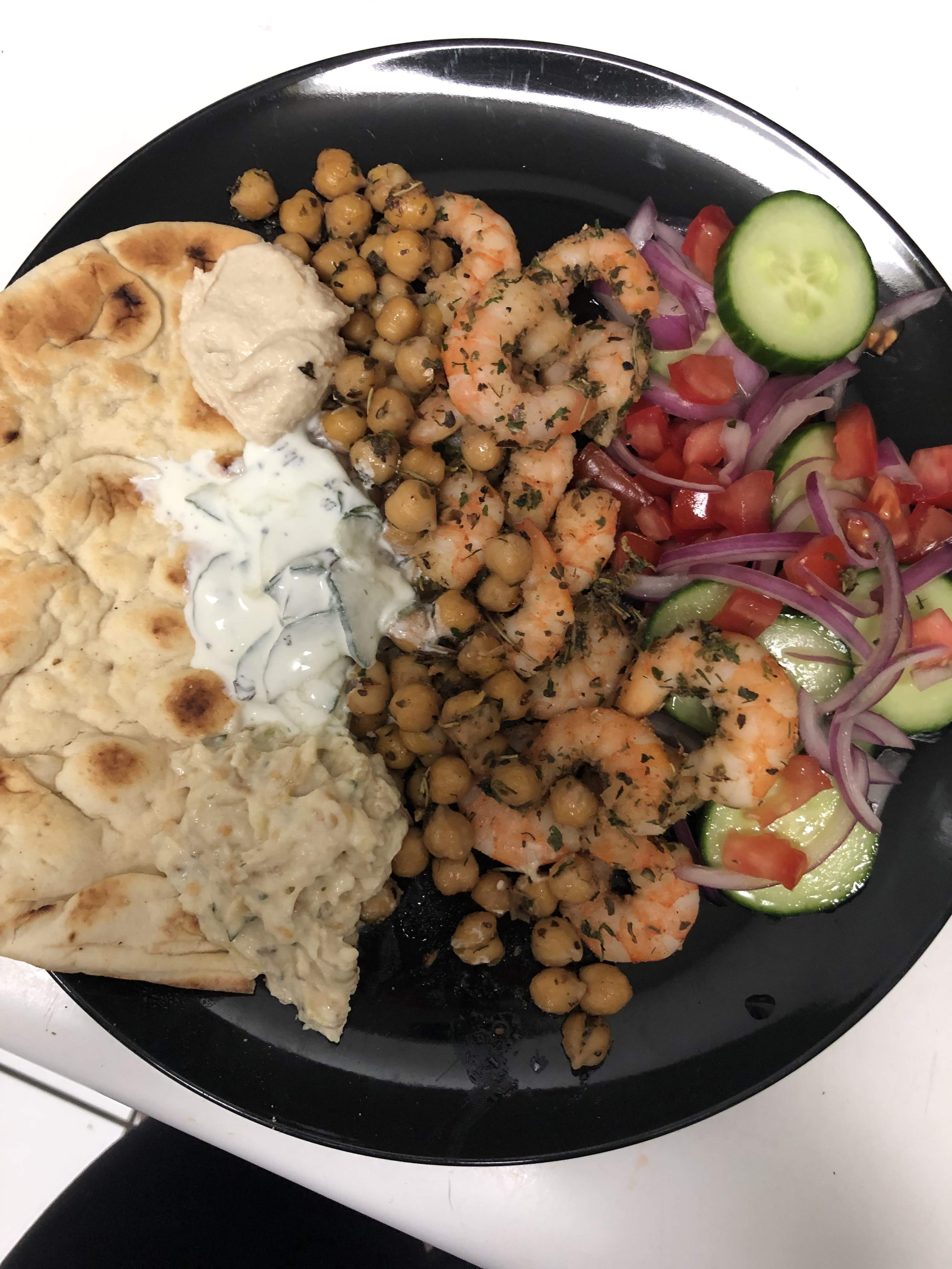 A black plate with chickpeas, a pita with sauces, shrimp, and a salad with cucumber, tomato and onion.