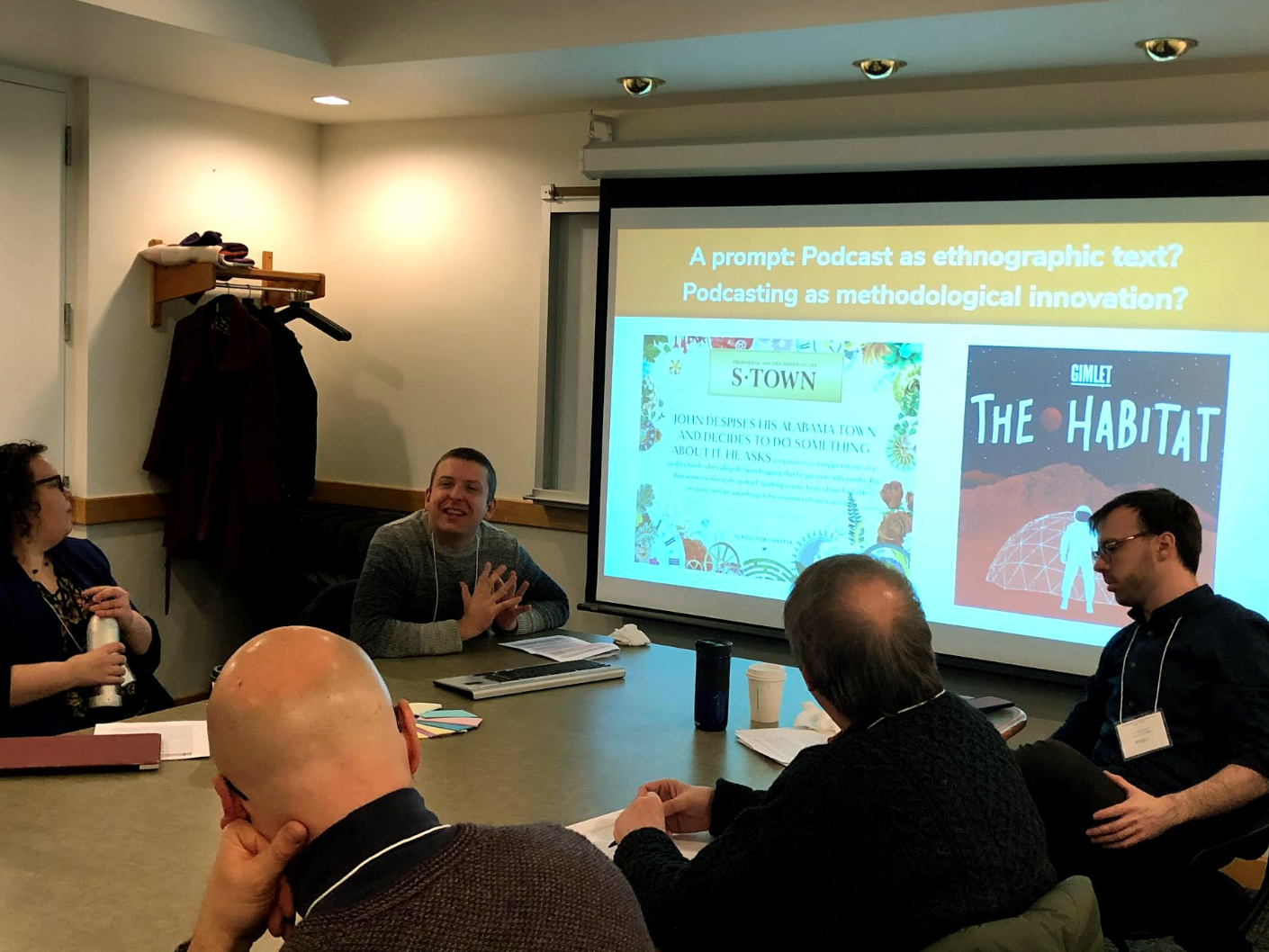 image of 5 people seated around a conference table making conversation. There is a screen in the background which has a slide up which says: A prompt Podcast as ethnographic text? Podcasting as methodological innovation?